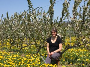 Suzanne Blatt sitting in an orchard